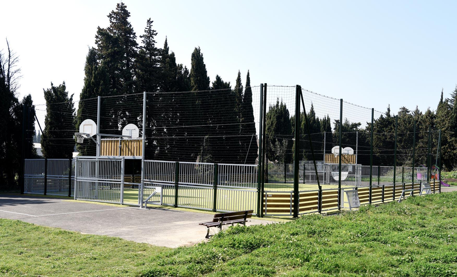 Intégration d'un terrain multisports complet (filet pare-ballons, gazon synthétique, pratique du football, basket, handball, volley)